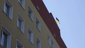 Flag of Ukraine on the building. Flag of Ukraine waving on the building stock footage