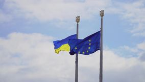 Flag of Ukraine and Europe. Flag of Ukraine and flag of European Union fluttering on a background of a cloudy sky stock video footage