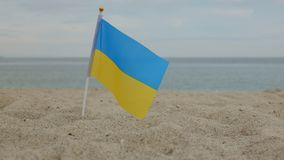 Flag of Ukraine, standing in the sand, against the background of the sea. royalty free stock photos