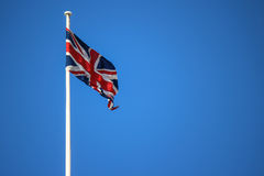 Flag of Union jack. Union jack flag with flag pole wind blown showing motion against a blue sky background Royalty Free Stock Photography
