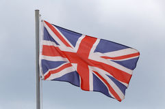 Flag of United Kingdom. Against cloudy sky Royalty Free Stock Photo