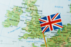 Flag of United Kingdom. Immigration concept - UK paper flag pin in the background of the United Kingdom map Royalty Free Stock Photo
