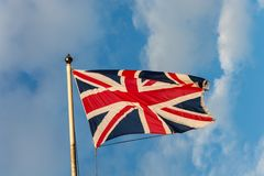 The flag of the United Kingdom on a pole and blue sky. Isolated Royalty Free Stock Photos