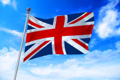 Flag of United Kingdom UK developing against a blue sky. Flag of United Kingdom UK developing against a clear blue sky royalty free stock image