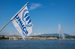 Flag of the United Nations High Commissioner for Refugees (UNHCR) waving in the wind on Geneva lake stock images