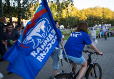 Flag of United Russia on a bicycle in the park. Flag Party United Russia with a bear on a bicycle in the park before the elections to the State Duma of Russia royalty free stock photos