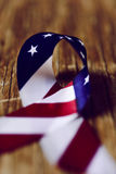 Flag of the United States of America. Closeup of an awareness ribbon made with a flag of the United States of America, on a rustic wooden surface Royalty Free Stock Image