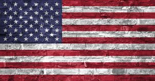 Flag of United States of America over an old brick wall background, surface. USA flag stock photography