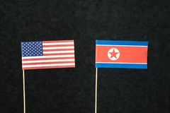 The flag of United States of America USA and North Korea. The flag of United States of America USA and North Korea made from paper on wooden stick against dark royalty free stock photography
