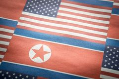 The flag of United States of America USA and North Korea. The flag of United States of America USA and North Korea on a wrinkled rough paper texture royalty free stock photos