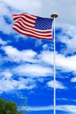 Flag of the United States. United States flag blowing in the breeze with blue sky and white clouds Stock Photo