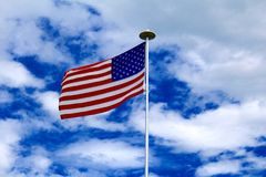 Flag of the United States. United States flag blowing in the breeze with blue sky and white clouds Stock Photos