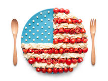 Flag of the United States made of tomato and salad. Round flag of the United States made of tomato and salad on a plate with wooden spoon and fork isolated on royalty free stock photo