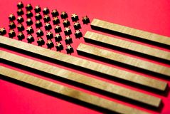 The flag of the United States on a red background made of wood, golden stripes on a red background stock photos