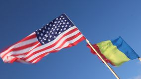 Flag of the United States and Romania. Waving in the wind on blue sky stock video footage