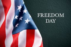 Text freedom day and american flag. The flag of the United States and the text freedom day against a dark green background Royalty Free Stock Photos