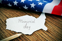 The flag of the United States and the text Memorial Day. A piece of paper in the shape of United States with the word Memorial Day written in it, placed on a Royalty Free Stock Photos