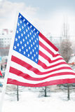 Flag of United States on wind at winter. Cloudy day in street of city Stock Image