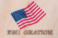 Flag of the United States, word emigration in abstract letters. Wooden background royalty free stock photo