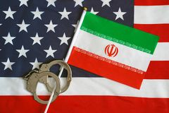 Flag of USA and Iran. Handcuffs. Sanctions. Iranian flag in handcuffs on the background of the American flag. US sanctions against Iran royalty free stock photography