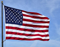 Flag USA waving in wind with blue sky and clouds Stock Image