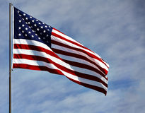 Flag USA in wind on blue sky and clouds Stock Images
