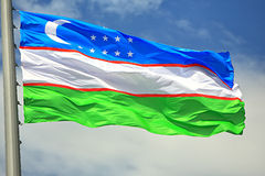Flag of Uzbekistan. Against the sky Stock Photography