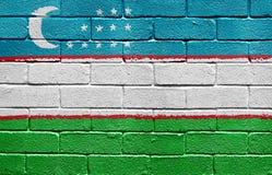 Flag of Uzbekistan on brick wall Stock Images