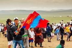 Flag vendor, Nadaam horse race. NADAAM HORSE RACE OUTSIDE ULAANBAATAR, MONGOLIA - JULY 12, 2010: Vendor selling Mongolian flags at Nadaam horse race, the most Stock Photography