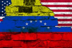 Flag of Venezuela and USA on a brick wall background with broken plaster stock image