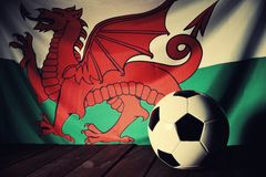 Flag of Wales with football on wooden boards. Royalty Free Stock Photos