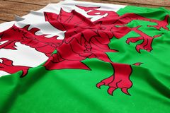 Flag of Wales on a wooden desk background. Silk Welsh flag top view stock illustration