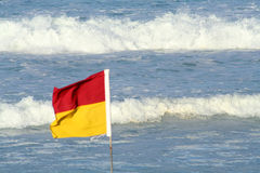 Flag & Waves. A Queensland life saving flag on the beach with waves in the background Royalty Free Stock Photo