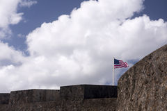 Flag waves over historic military fort. Royalty Free Stock Photography