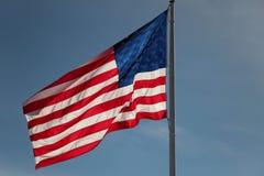 Flag waving against blue sky Stock Photo
