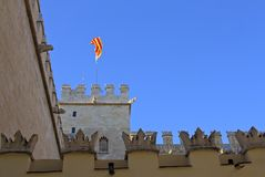 Flag waving in the historical building La Llotja. Valencia. Tower, flag and battlements of the historic building La Llotja. Valencia. Spain Stock Photos