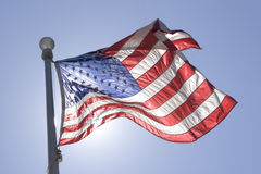 Flag waving in the wind. United States Flag waving in the wind with sun behind Stock Image