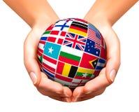 Flaga świat w kuli ziemskiej i rękach Zdjęcie Stock