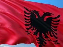 Flaga Albania falowanie w wiatrze przeciw g??bokiemu niebieskiemu niebu Wysokiej jako?ci tkanina fotografia royalty free