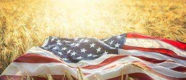 Flaga amerykańska kłama na złotym pszenicznym polu obrazy stock