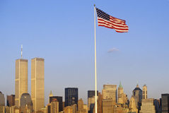 Flaga Amerykańska lata nad linią horyzontu Miasto Nowy Jork od Nowy Jork schronienia, NY obraz royalty free