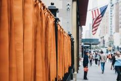 Flaga amerykańska na masztowych i pomarańczowych faborkach wiążących ogrodzenie na st obraz royalty free