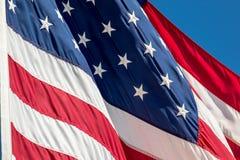 Flaga Amerykańska ozdabiająca z gwiazdami i lampas fala w wiatrze przeciw niebieskiemu niebu zdjęcie stock