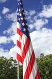Flaga amerykańska przeciw niebieskiego nieba i chmur tłu Obrazy Royalty Free