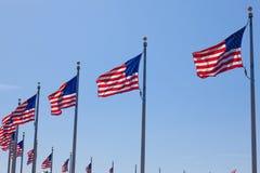Flaga amerykańskie - gwiazdowy i lampasy unosi się nad chmurnym niebieskim niebem Obraz Royalty Free