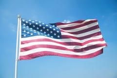 Flaga Amerykańskiej falowanie w Jaskrawym niebieskim niebie zdjęcia stock
