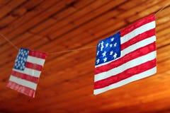 Flaga amerykańskiej obwieszenie na niciach przeciw tłu drewniany sufit obraz stock