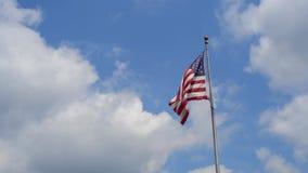 Flaga ameryka?skiej falowanie na niebieskiego nieba tle
