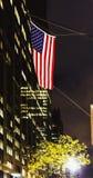 Flaga amerykańskiej falowanie od Manhattan ` s Nowy Jork budynków przy ni Obrazy Royalty Free