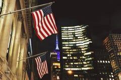 Flaga amerykańskiej falowanie od Manhattan ` s Nowy Jork budynków przy ni Obraz Royalty Free